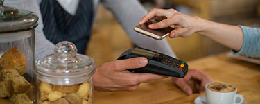 Woman paying bill through smartphone using NFC technology